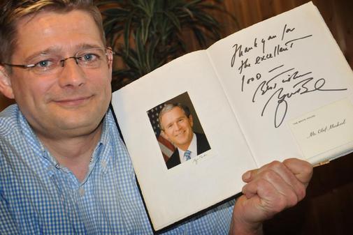 Foto: Olaf Micheel mit Gästebucheintrag von Bush